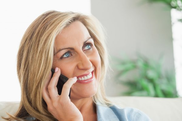 25819374 - smiling blonde woman calling someone with her mobile phone in a living room